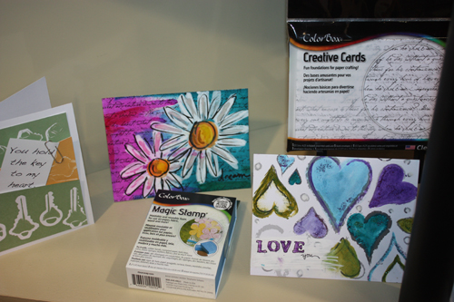 Simply decorate the preprinted cards by spraying or stamping over the design then layering embellishments onto dry card.
